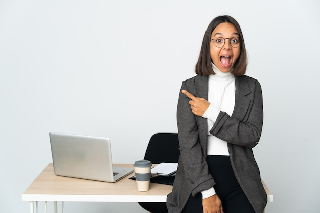 사무실에서 일하는 젊은 라틴 비즈니스 여자는 놀란 측면을 가리키는 흰 벽에 고립