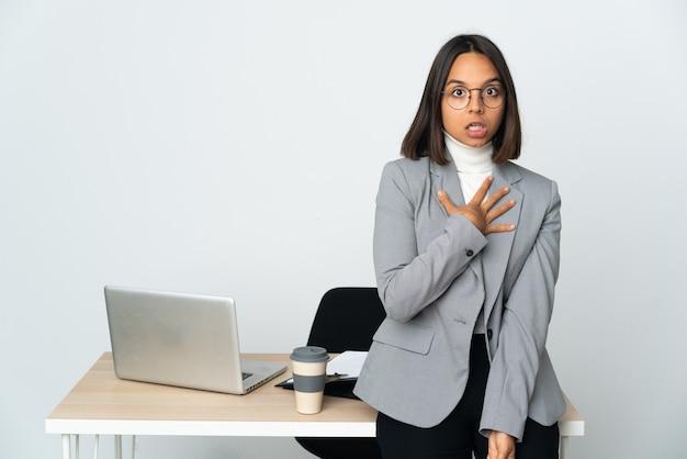 흰 벽에 고립 된 사무실에서 일하는 젊은 라틴 비즈니스 여자는 놀라게하고 오른쪽을 보면서 충격