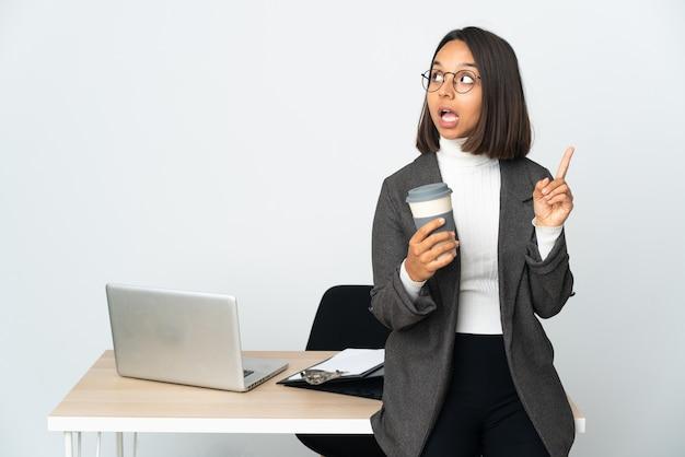 손가락을 가리키는 아이디어를 생각하는 흰 벽에 고립 된 사무실에서 일하는 젊은 라틴 비즈니스 여자
