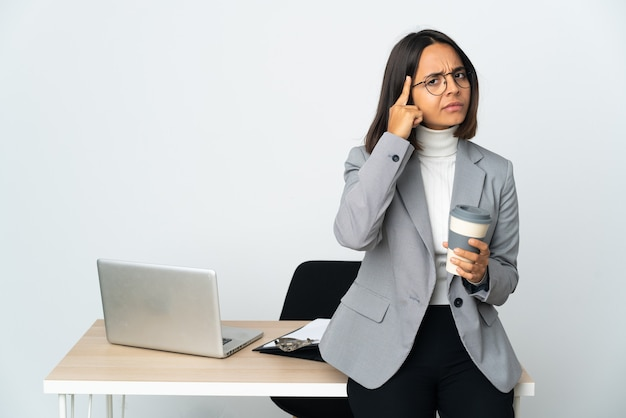 아이디어를 생각하는 흰 벽에 고립 된 사무실에서 일하는 젊은 라틴 비즈니스 여자