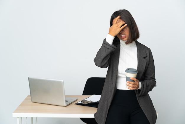 두통과 흰 벽에 고립 된 사무실에서 일하는 젊은 라틴 비즈니스 우먼