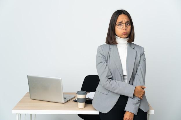 슬픈 표정으로 흰 벽에 고립 된 사무실에서 일하는 젊은 라틴 비즈니스 여자