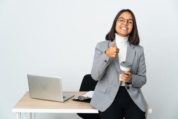 좋은 일이 일어났기 때문에 엄지 손가락으로 흰색에 고립 된 사무실에서 일하는 젊은 라틴 비즈니스 여자