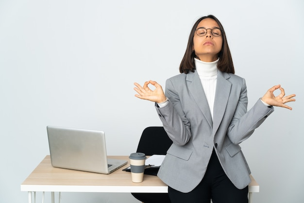 Young latin business woman working in a office isolated on white background in zen pose
