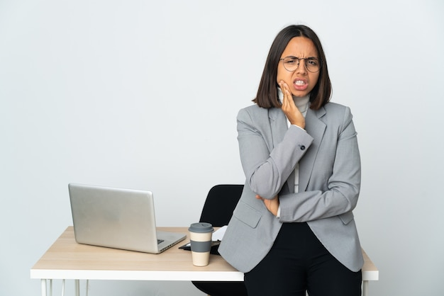 Young latin business woman working in a office isolated on white wall with toothache