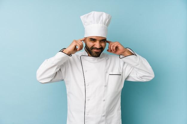 Молодой латинский шеф-повар изолировал уши руками.