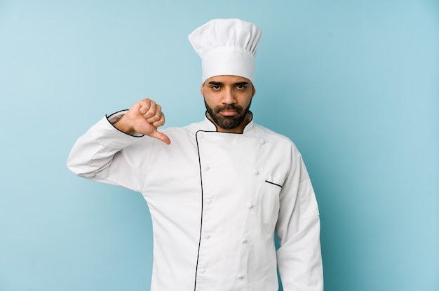 Молодой человек латинского шеф-повара изолировал показывая жест неприязни, большие пальцы руки вниз. концепция несогласия.