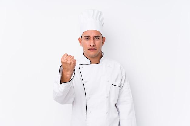 젊은 라틴 요리사 남자 절연 보여주는 주먹 카메라, 공격적인 표정.