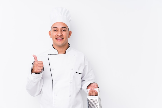 Young latin chef man smiling and raising thumb up