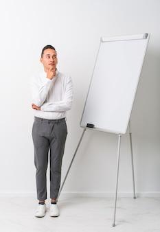ホワイトボードを持った若いラテン系コーチの男は、疑わしく懐疑的な表情で横向きに孤立しました。