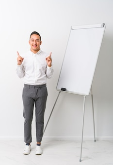 Young latin coaching man with a whiteboard isolated indicates with both fore fingers up showing a blank space.