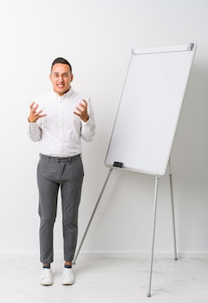 Young latin coaching man with a whiteboard isolated upset screaming with tense hands.