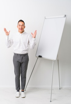 Young latin coaching man with a whiteboard receiving a pleasant surprise, excited and raising hands.