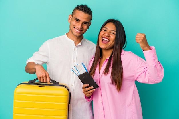 勝利、勝者の概念の後に拳を上げる青い背景に孤立して旅行に行く若いラテンカップル。