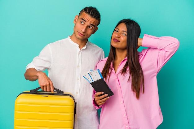 頭の後ろに触れて、考えて、選択をする青い背景に孤立して旅行に行く若いラテンカップル。