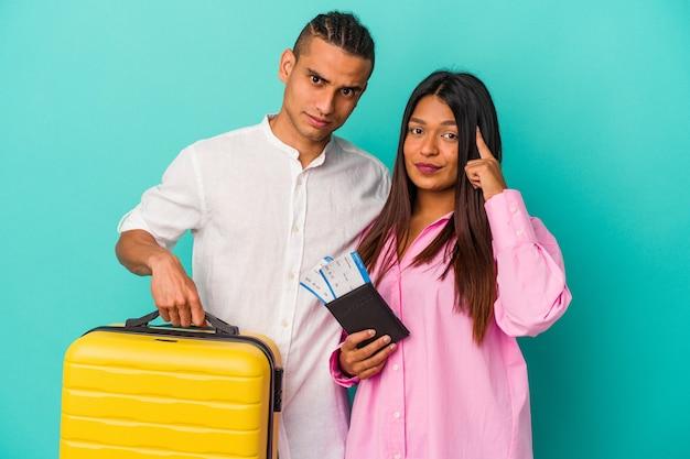 ラテン系の若いカップルは、青い壁に孤立して旅行に行き、指で寺院を指して、考え、仕事に集中しました。