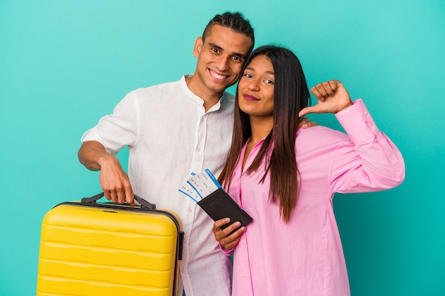 Young latin couple going to travel isolated on blue background feels proud and self confident, example to follow.