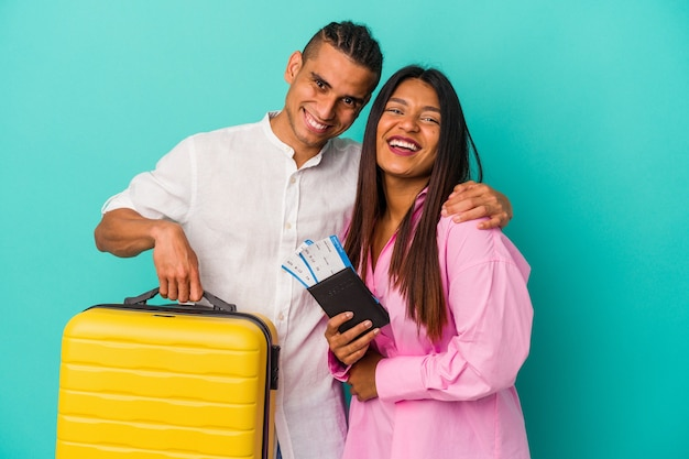 Young latin couple going to travel isolated on blue background laughing and having fun.