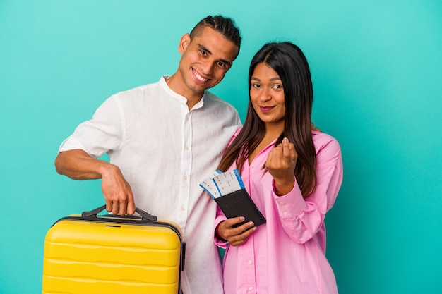 Young latin couple going to travel isolated on blue background pointing with finger at you as if inviting come closer.