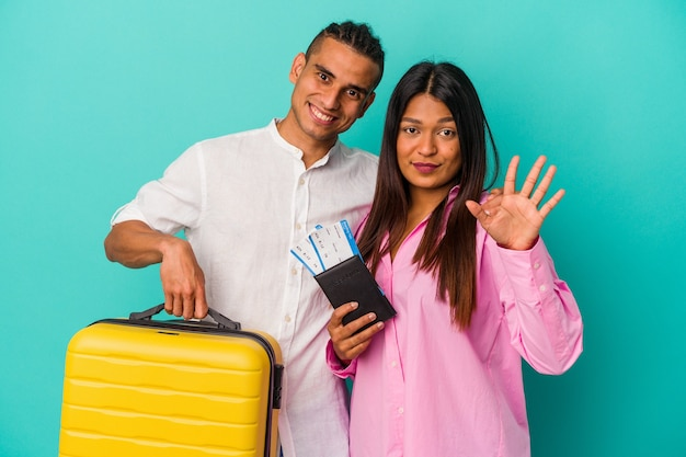 Young latin couple going to travel isolated on blue background smiling cheerful showing number five with fingers.