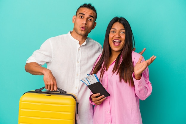 Young latin couple going to travel isolated on blue background surprised and shocked.