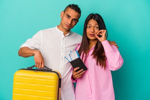 Young latin couple going to travel isolated on blue background with fingers on lips keeping a secret.