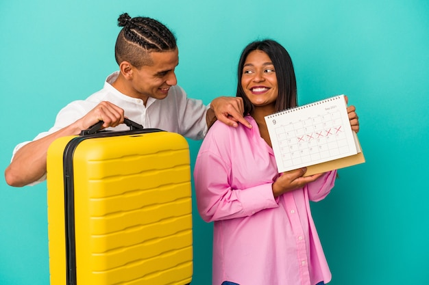Young latin couple going to travel isolated on blue background