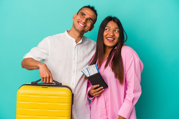 Young latin couple going to travel isolated on blue wall dreaming of achieving goals and purposes
