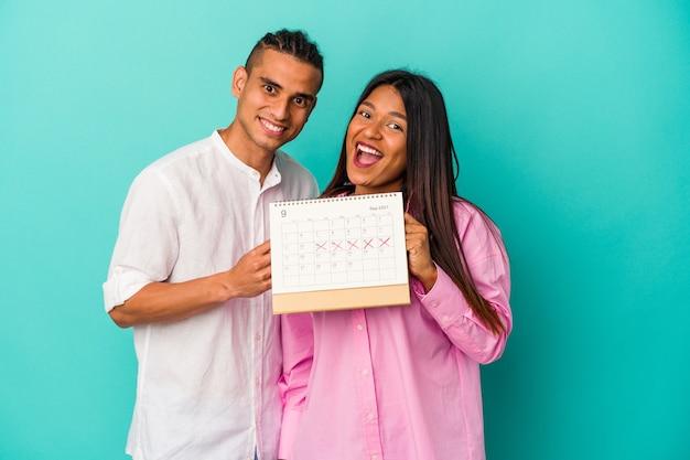 青い背景で隔離のカレンダーを保持している若いラテンカップル