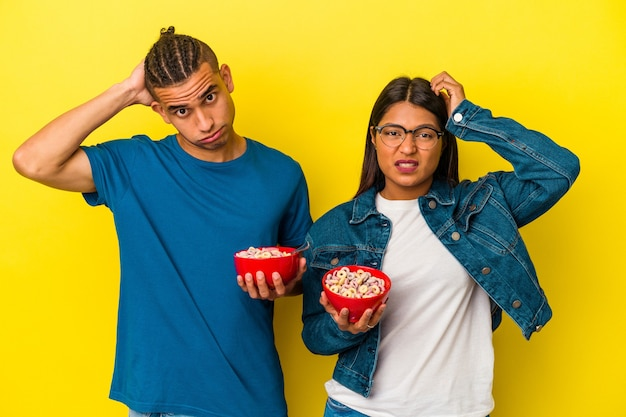 ショックを受けている黄色の背景に分離されたシリアルボウルを保持している若いラテンカップル、彼女は重要な会議を思い出しました。 Premium写真