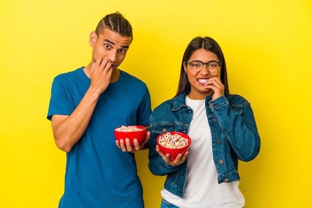 노란색 배경에 격리된 시리얼 그릇을 들고 있는 젊은 라틴 커플은 손톱을 물어뜯고 긴장하고 매우 불안해합니다.