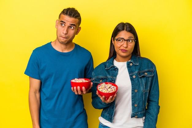 黄色の背景に分離されたシリアルボウルを保持している若いラテンカップルは混乱し、疑わしく、不安を感じています。