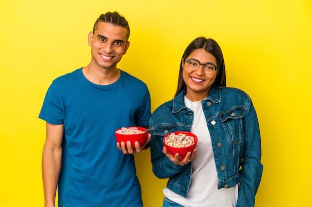 黄色の背景に分離されたシリアルボウルを保持している若いラテンカップル幸せ、笑顔、陽気な。