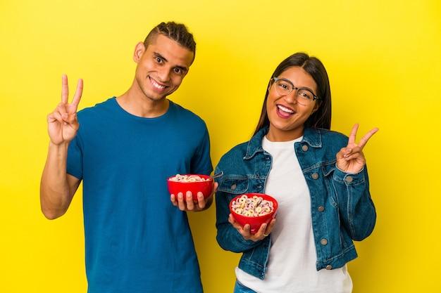 黄色の背景に分離されたシリアルボウルを持っている若いラテンカップルは、指で平和のシンボルを示して楽しくてのんきです。