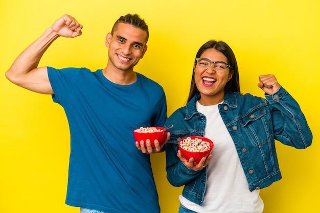 勝利、勝者の概念の後に拳を上げる黄色の背景に分離されたシリアルボウルを保持している若いラテンカップル。