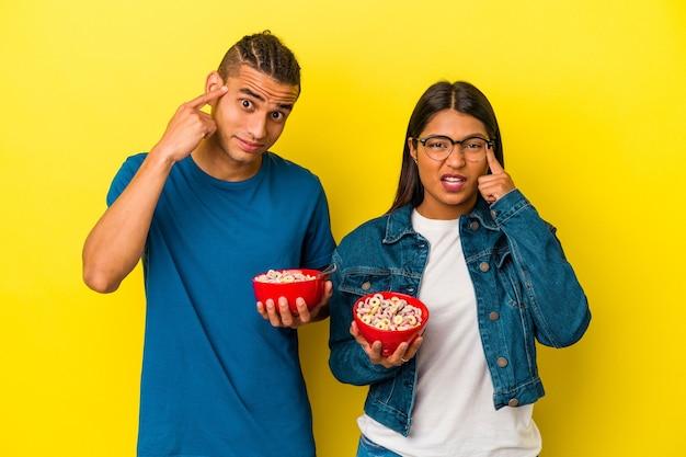 人差し指で失望のジェスチャーを示す黄色の背景に分離されたシリアルボウルを保持している若いラテンカップル。