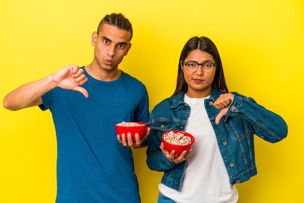 嫌いなジェスチャーを示す黄色の背景に分離されたシリアルボウルを保持している若いラテンカップルは、親指を下に向けます。不一致の概念。
