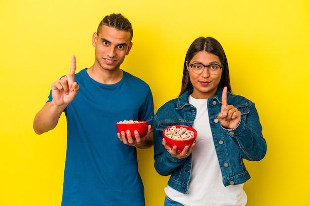 指でナンバーワンを示す黄色の背景に分離されたシリアルボウルを保持している若いラテンカップル。