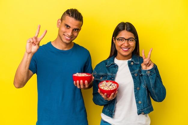 指で2番目を示す黄色の背景に分離されたシリアルボウルを保持している若いラテンカップル。