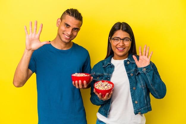 黄色の背景に分離されたシリアルボウルを持っている若いラテンカップルは、指で5番を示して陽気に笑っています。