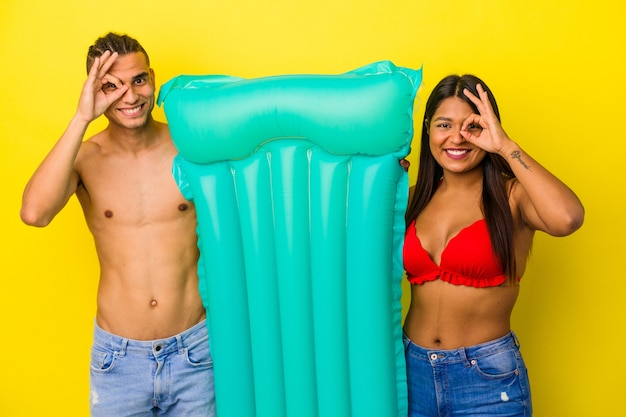 Young latin couple holding air mattress isolated on yellow background excited keeping ok gesture on eye.