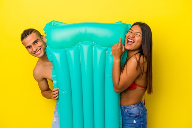 Young latin couple holding an air mattress isolated on yellow background