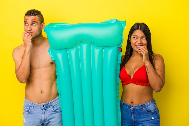 Young latin couple holding air mattress isolated on yellow wall relaxed thinking about something looking at a copy space.