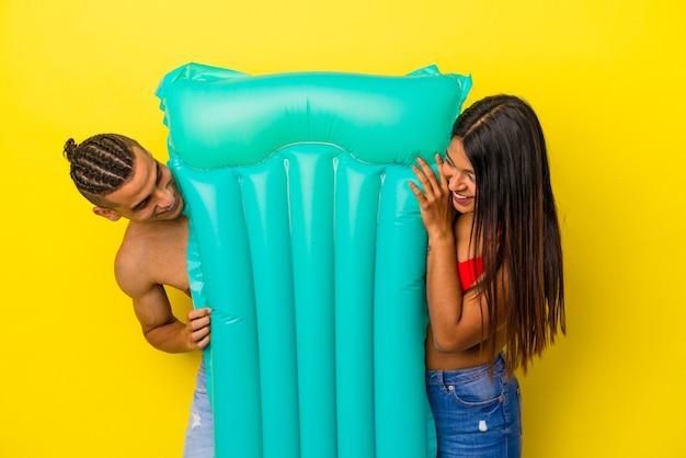 黄色の背景で隔離のエアマットレスを保持している若いラテンカップル