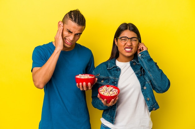 Young latin couple holding a cereals bowl isolated on yellow background covering ears with hands.