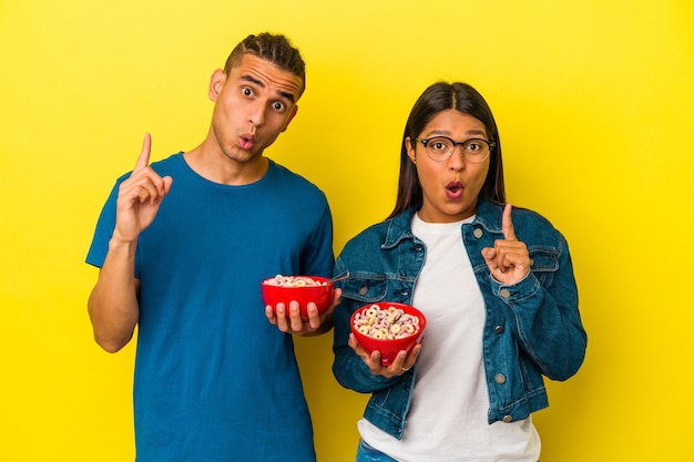 Young latin couple holding a cereals bowl isolated on yellow background having some great idea, concept of creativity.