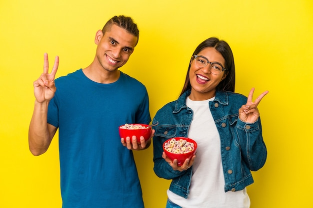 Young latin couple holding a cereals bowl isolated on yellow background joyful and carefree showing a peace symbol with fingers.