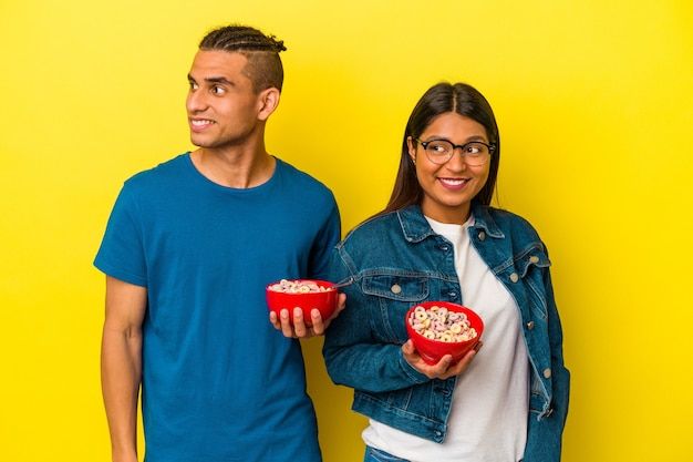 Young latin couple holding a cereals bowl isolated on yellow background looks aside smiling, cheerful and pleasant.