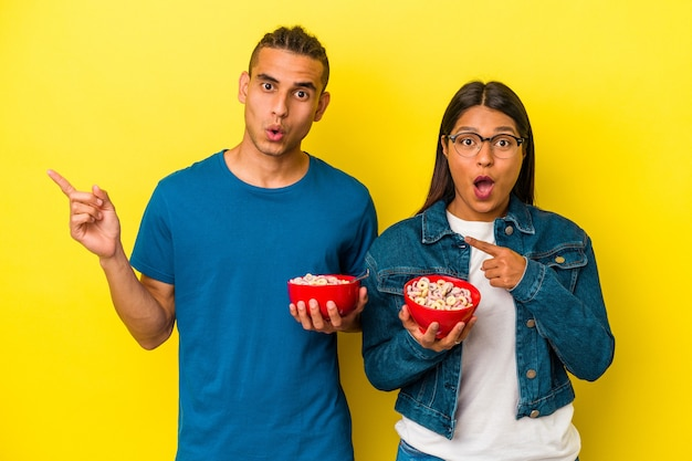 Young latin couple holding a cereals bowl isolated on yellow background pointing to the side