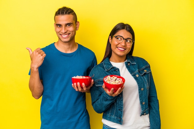 Young latin couple holding a cereals bowl isolated on yellow background points with thumb finger away, laughing and carefree.